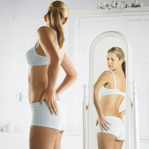 Woman in Underwear Looking at Her Reflection in a Mirror