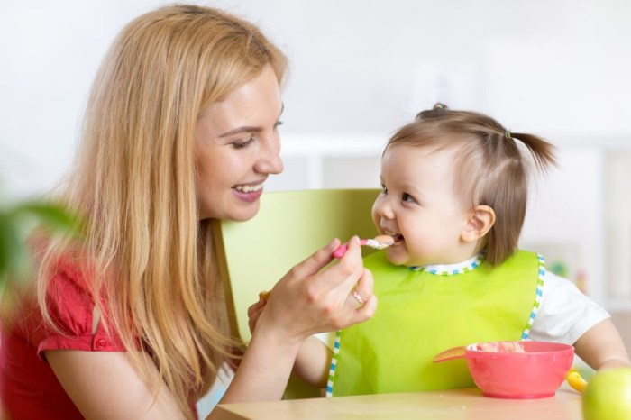 Happy mother spoon feeding her baby child in nursery